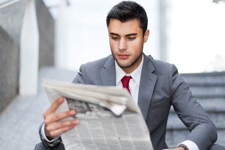 job advertisement: Portrait of a young business man reading a newspaper outdoor