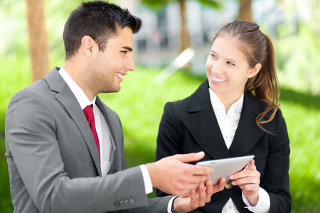 Couple of business people using a tablet outdoor photo