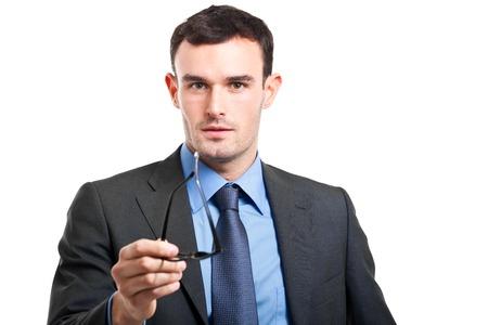 Smiling businessman holding glasses on white background photo