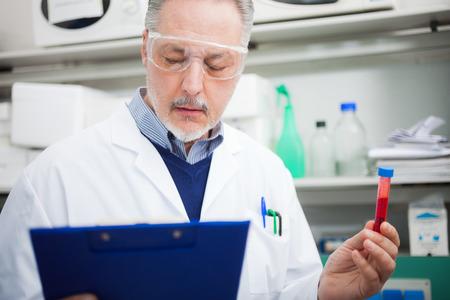 examenes de laboratorio: M�dicos de la lectura de un documento en posesi�n de un tubo de ensayo en un laboratorio Foto de archivo