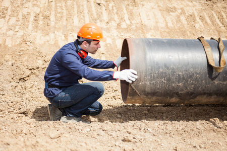 Man examining a pipe in a construction site photo