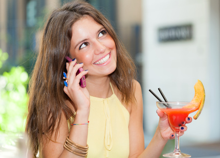 Portrait of a young woman drinking a cocktail and talking on the phone photo