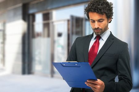 quality work: Portrait of a businessman holding a clipboard