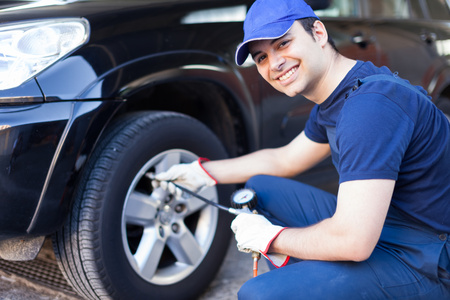Smiling mechanic inflating a tire photo