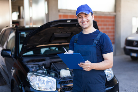 mechanic: Smiling mechanic writing on a clipboard Stock Photo