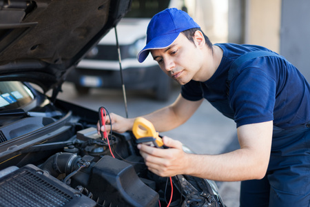 Auto electrician troubleshooting a car engine Stock Photo