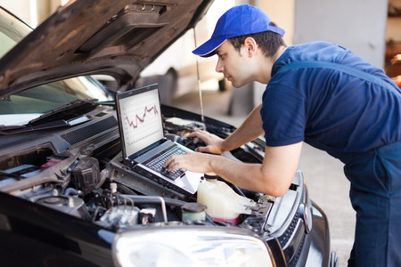 Skilled mechanic using a laptop computer to check a car engine Zdjęcie Seryjne