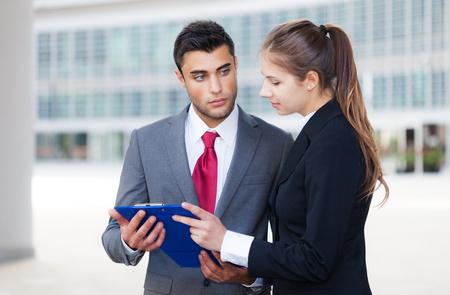 personas leyendo: Los j�venes de negocios la lectura de un documento