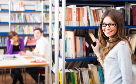 Portrait of a student taking a book from a bookshelf photo