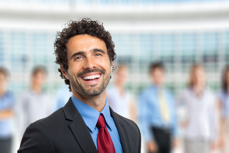 small group of people: Smiling leader in front of a group of business people