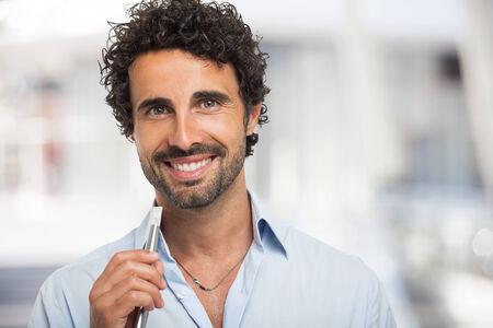 e cigarette: Smiling man holding an electronic cigarette
