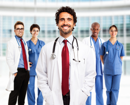 school nurse: Portrait of a smiling doctor in front of his team Stock Photo