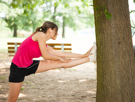 Woman stretching her leg against a tree Stock Photo