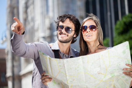 Happy couple of tourists holding a map photo