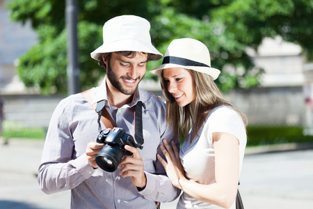 Tourist showing holiday pictures to his girlfriend photo