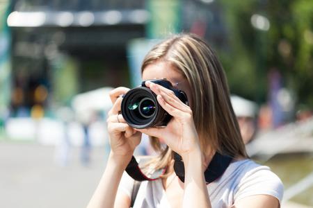 Portrait of a female photographer using a camera photo
