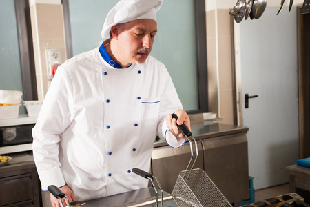 fryer: Male chef dressed in white uniform using a deep fryer Stock Photo