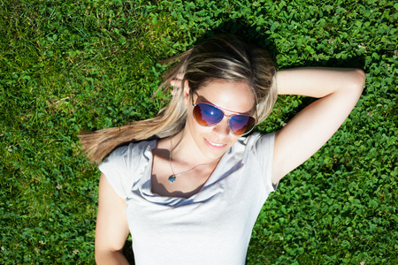sun down: Young smiling woman sunbathing on the grass