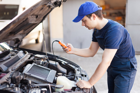 Mechanic using an electronic tester on a car engine photo
