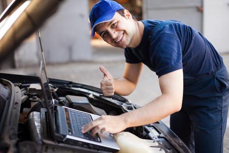mechanic: Sonriendo mecánico que usa una computadora portátil para revisar un motor de coche