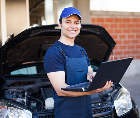 Smiling mechanic using a laptop computer to check a car engine photo