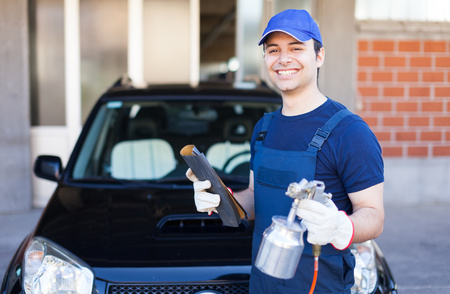 Car body repairer holding a spray gun and a sheet of sandpaper photo
