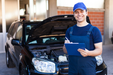 automotive repair: Smiling mechanic writing on a clipboard Stock Photo
