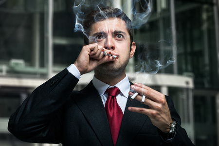 angry businessman: Portrait of a nervous businessman smoking many cigarettes at once