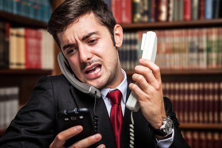 Stressed businessman talking on many phones at once Stock Photo