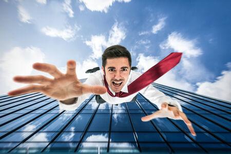 hombre cayendo: Hombre de negocios que cae desde un edificio Foto de archivo
