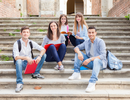 Group of smiling students sitting on a staircase photo