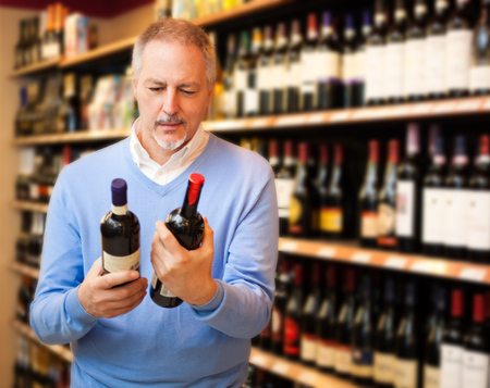Man in a supermarket choosing the right wine photo