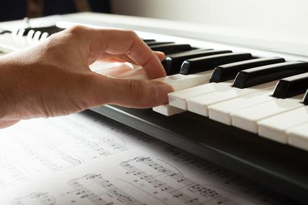 Detail of an hand pressing piano keys photo