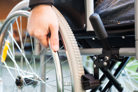 wheelchair man: Paralyzed man using his wheelchair Stock Photo