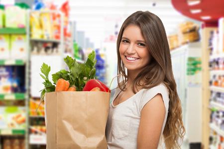 과일과 야채의 전체 종이 쇼핑 가방을 들고 건강한 긍정적 인 행복한 여자