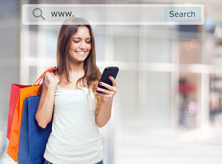 web shop: Young woman holding shopping bags and a mobile phone