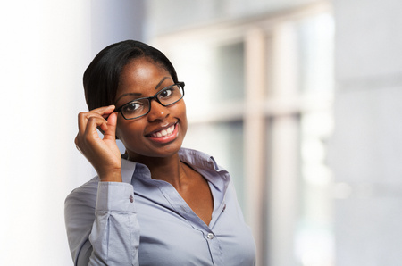 african business woman: Young smiling black woman holding her eyeglasses