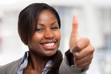 Very happy young woman giving thumbs up photo