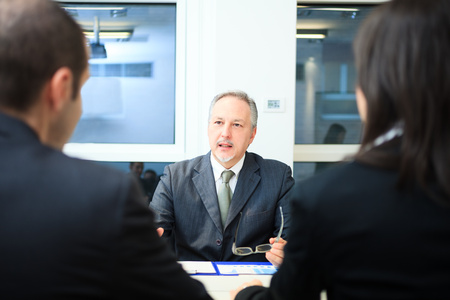 bank manager: Businessman talking to a couple in a office