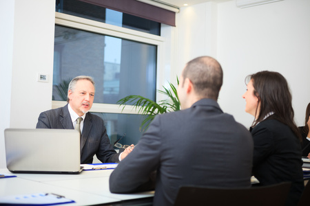 bank office: Businessman talking to a couple in a office