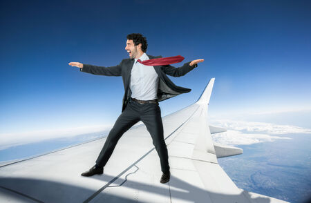 Fearless businessman riding an airplane photo