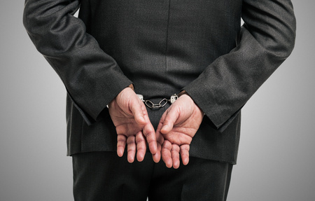 Handcuffed businessman, concept for white collar crime photo