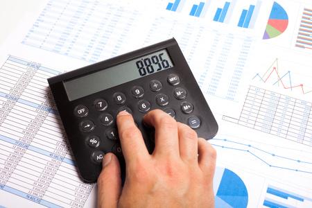 Businessman examining financial charts using a calculator photo