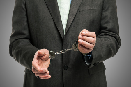 white collar crime: Handcuffed businessman, concept for white collar crime