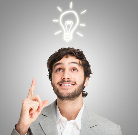 idée: Jeune homme souriant avoir une bonne idée