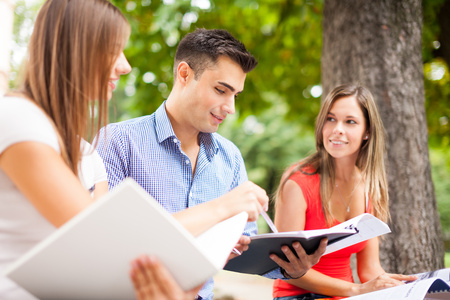 Outdoor portrait of three smiling students studying in a park photo
