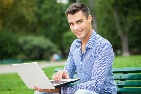 Young smiling man using a laptop computer outdoors photo