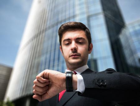 puntual: Joven hombre de negocios mirando su reloj