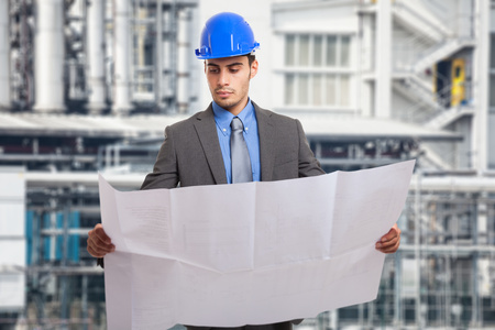 oil and gas industry: Portrait of an engineer holding a blueprint