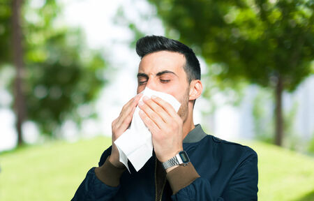 catarrh: Young man blowing his nose